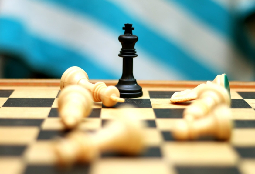 Black chess piece surrounded by fallen white pieces